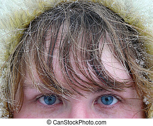 woman\'s blue eyes and hair under snow