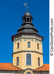 tower of the castle in Nesvizh on a background of blue sky -...