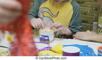 Little child makes crafts toys from cardboard at table in...