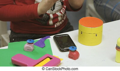 Little girl makes crafts toys from cardboard at table in the...