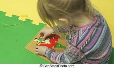 Child collects a picture puzzle on the floor in kindergarten...