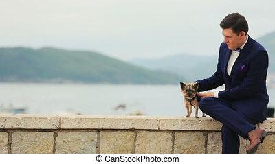 Handsome groom petting little cute dog terrier Montenegro,...