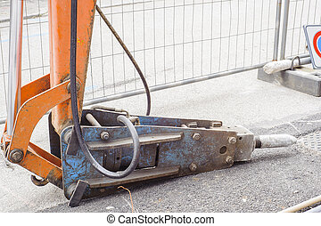 Large pneumatic hammer mounted on the hydraulic arm of a...