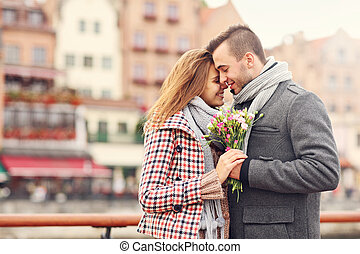 Romantic couple with flowers in the city