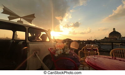 Young loving couple kissing in the vintage car on the rooftop cafe with glasses of red wine and flowers on the table. View of ancient city building while raining. Romantic sunset on the background