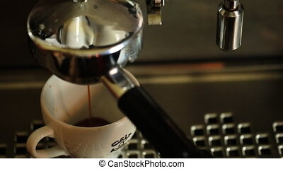 Coffee maker filling espresso in a cup on white.