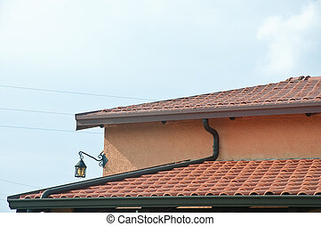 Roof of a house with roof tiles and gutters