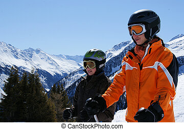 A woman and a child about a super ski with skis down to go.