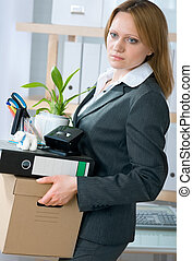 unemployment concept - A fired woman in a suit carrying a...