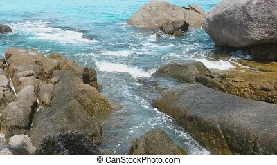 Turquoise rolling wave slamming on the rocks of the...
