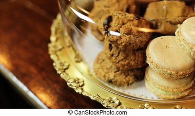 Some macaroons and cookies in a glass bell jar