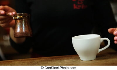 brewed coffee is poured from a copper turk coffee in a white...