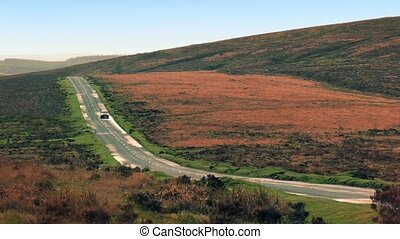 Car Drives Down Hill In Wilderness - Car passes on an empty...