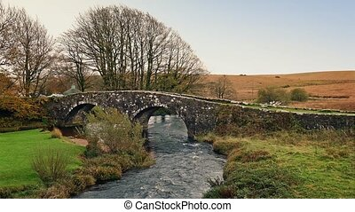 Car Passes Over Old Stone Bridge - Car on rustic bridge over...