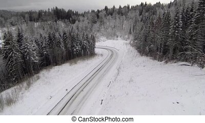 Aerial shot of snow-covered road in the countryside...