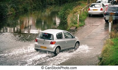 Cars Drive Through Waterway - Several cars driving through...