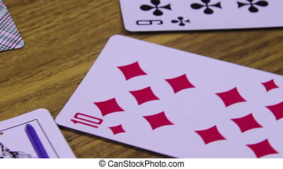 Playing Cards Rotates on a Wooden Table - Playing cards of...
