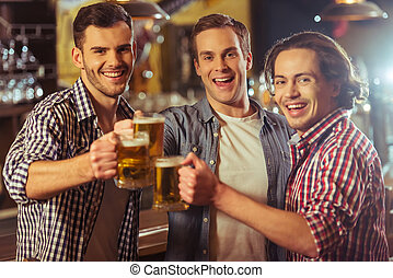 Men in pub - Three young men in casual clothes are smiling,...
