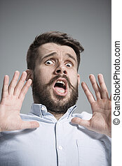 Man is looking scared Over gray background - Man wearing a...