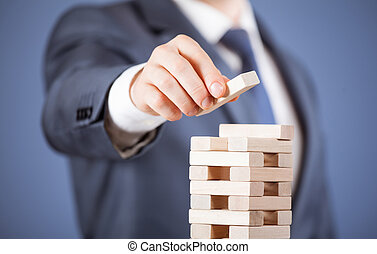 Unrecognizable businessman forming a wooden pyramid -...