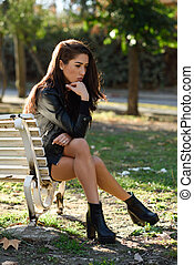 Thoughtful woman sitting alone outdoors Girl worried in an...