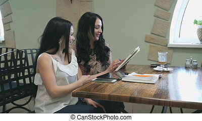 Two girls look at pictures on digital tablet