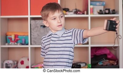 Little boy photographing himself makes selfie
