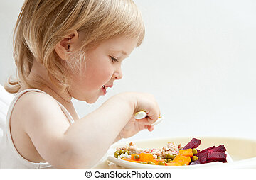 Adorable baby girl eating fresh vegetables; healthy eating...