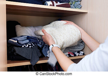 takes out wool sweater with wardrobe - takes out clothing...