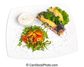 A piece of grilled salmon with lettuce, tomatoes, olives and white sauce on a plate