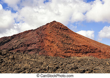 Red volcano with solidified lava in the foreground in...