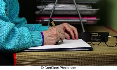 Old woman writing on the paper near table