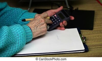 Old woman writes and use calculator