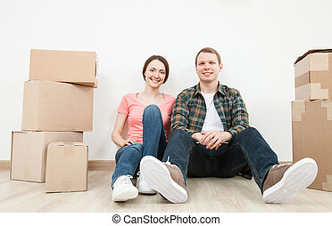 Happy young man and woman sitting near cardboard boxes,...