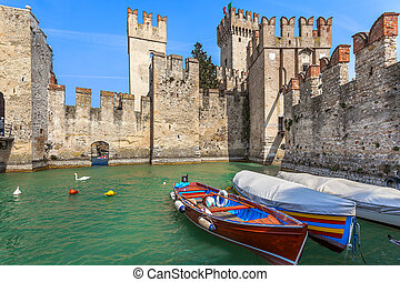 Old castle in Sirmione, Italy. - Boats on lake Garda and...