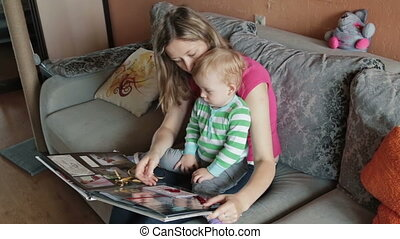Mother watching with her son photo album - Family watching...