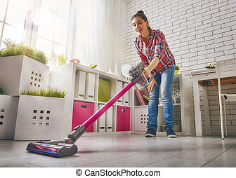 Woman vacuums the floor - Beautiful young woman makes...