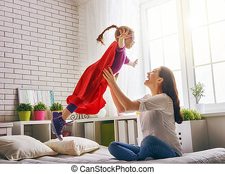 Mother and her child girl playing together. Girl in an...