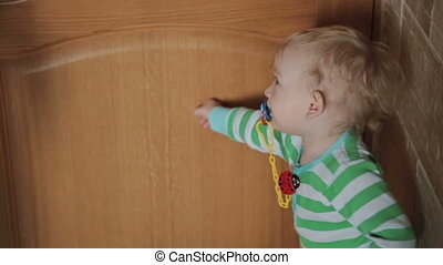 Little boy close and open the door at home