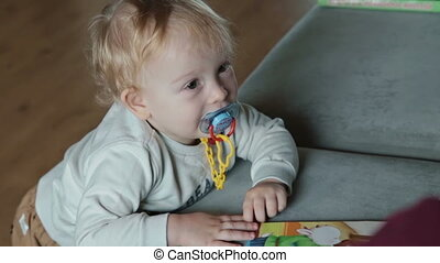 Boy stay near the sofa at home - Little blondy boy stay near...