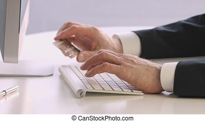 Male hands holding a credit card at a keyboard during online shopping.