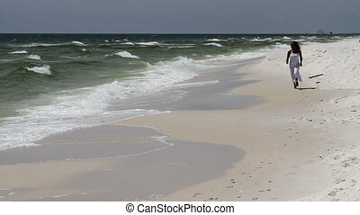 Woman In White Runs Beach - Attractive black woman runs...