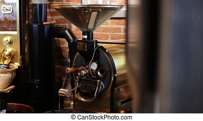 Freshly roasted coffee beans mixing in a coffee roaster -...