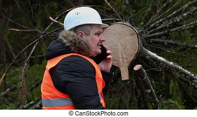 Forest inspector talking on smartphone near tree