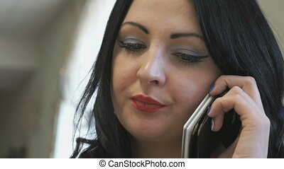 Business lady talks on the phone in cafe Closeup