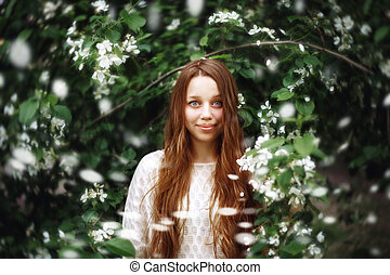 Young Woman among Spring Flowers Outdoors - Dreamy Portrait...