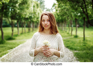 Young Woman Holding Flowers Outdoors - Dreamy Portrait of...