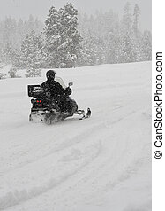 Snowmobiling - A lone driver on a snowmobile traveling...