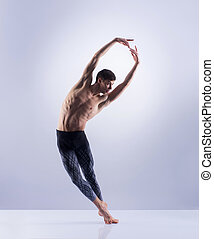 Athletic ballet dancer performing in a studio - Athletic...