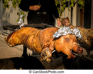 Roasted Pig on Spit - Two roasting pigs on spit outdoors at...